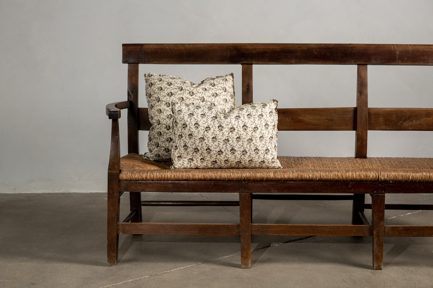 Two Howe Rambling Rose Nickey Kehoe Collection pillows on a bench.