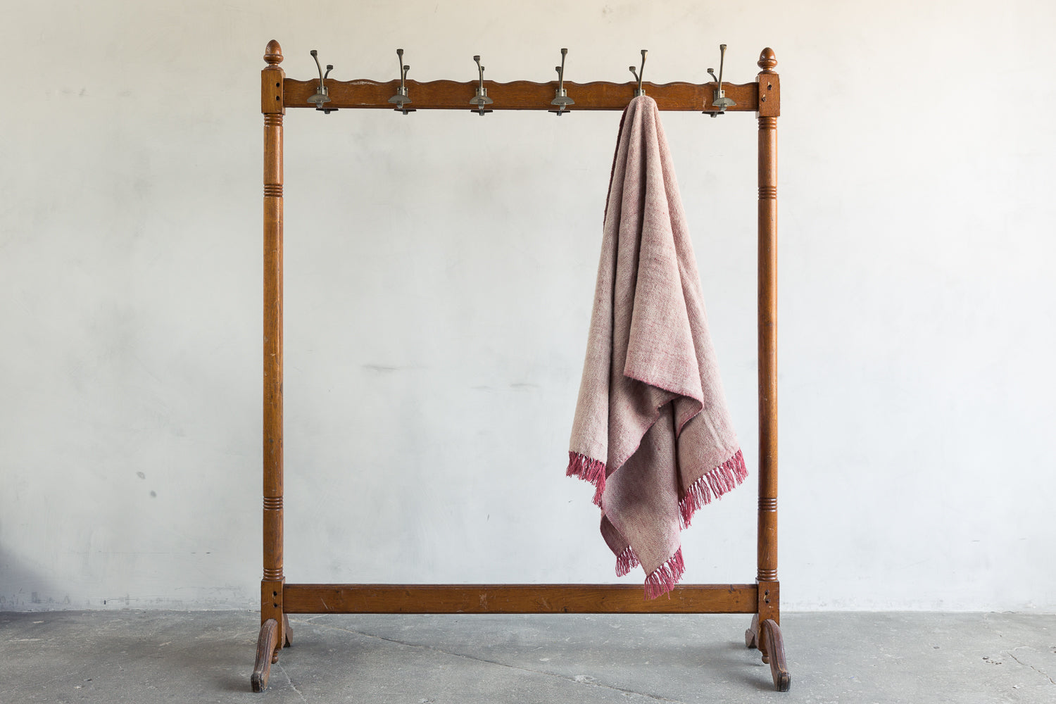 One Rose Neem Tarak Wool Throw on a rack.