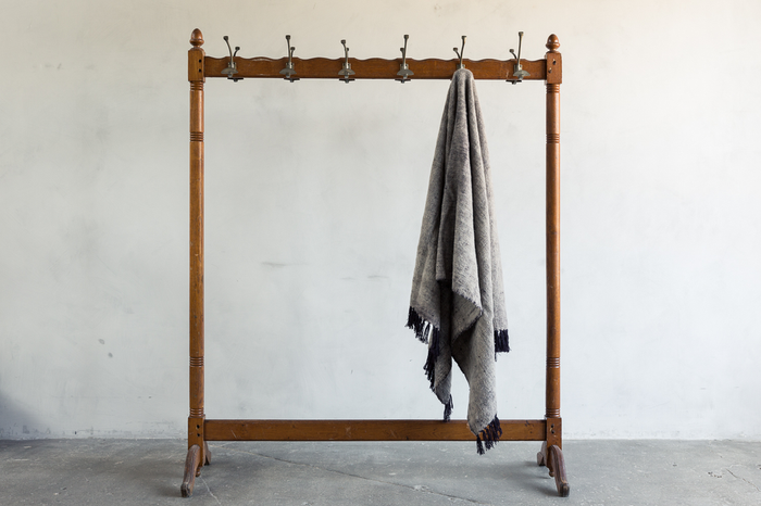 One Potters Cla Neem Tarak Wool Throw on a rack.