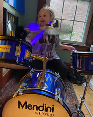 little girl playing the drums