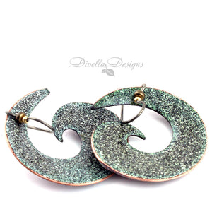 Back view of black, copper and yellow spiral shaped boho earrings by Divella Designs. The ear wires are niobium.