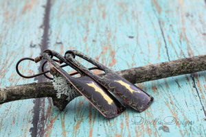 Rectangular Boho Earrings in Black, Copper & Gold on niobium ear wires laying on a branch