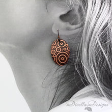 Load image into Gallery viewer, boho copper earrings with circular pattern on model