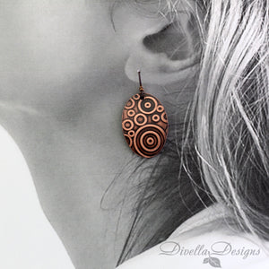 boho copper earrings with circular pattern on model