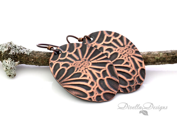 copper boho earring with floral motif on a branch
