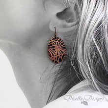 Load image into Gallery viewer,  copper boho earring with floral motif on a model