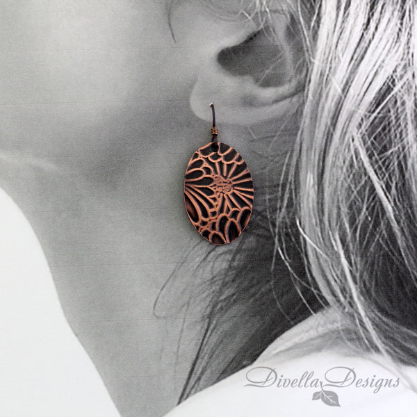 copper boho earring with floral motif on a model