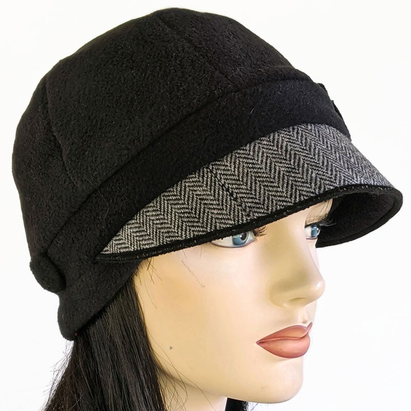Fleece cap in black with herringbone visor, pin trim and ear saver buttons
