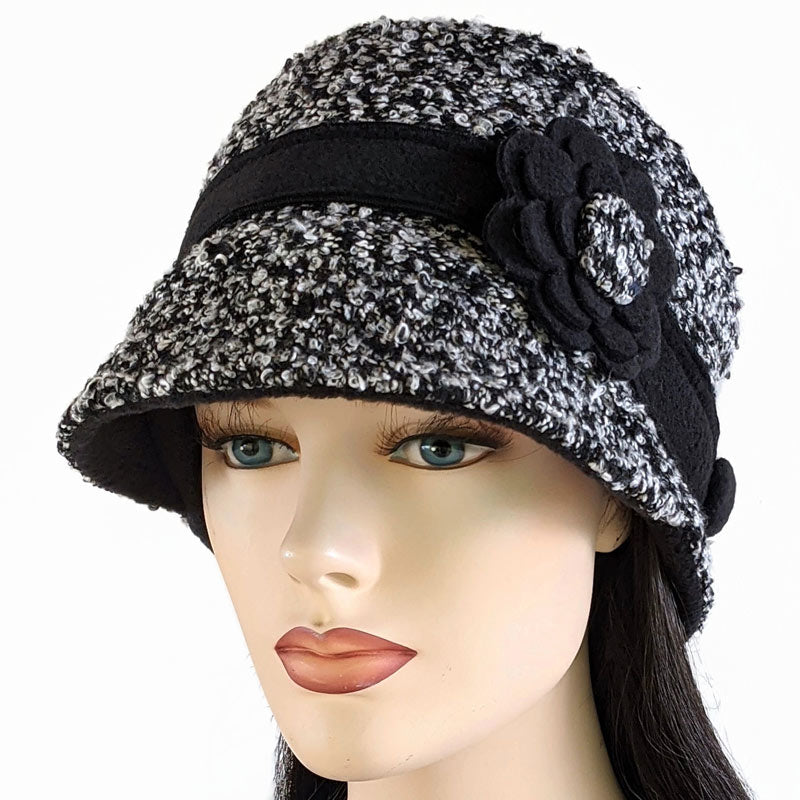 Cap with visor and floral pin, with ear saver buttons in black and white boucle