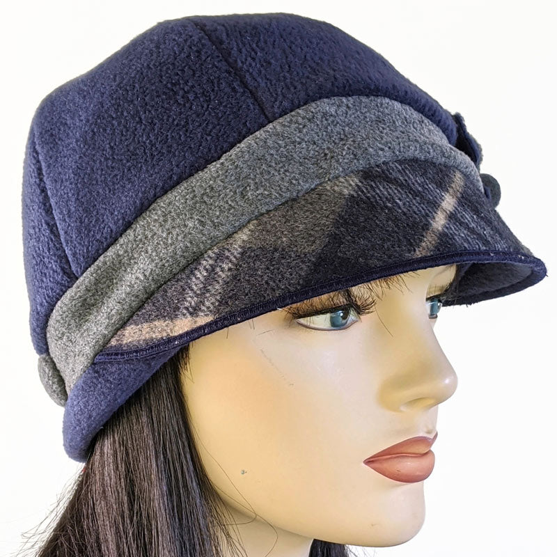 Fleece cap in navy and charcoal with plaid visor, pin and ear saver buttons