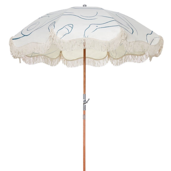 Business & Pleasure Le Basque Premium Beach Umbrella. White fabric with a blue line design and white frills hanging from the ends. The pole is brown wood with silver metal hardware