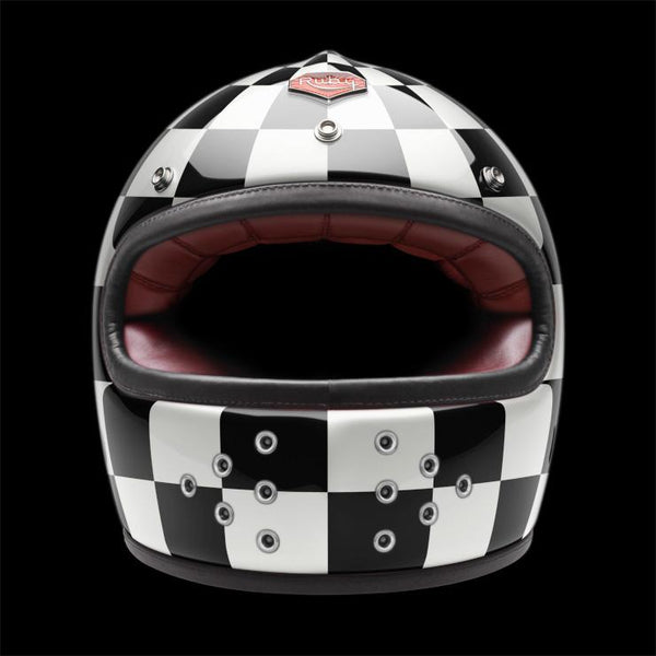Ruby Motorcycle Helmet. Full carbon shell Sheepskin leather lined comfort foam interior 7 ventilation channels in crown of helmet 2 exhaust ports at back of neck roll 12 ventilation holes on the chin guard Hand painted Leather trimmed eyeport 3 shell sizes: XS-S, M-L, XL-2XL DOT approved. Black and white checker design.