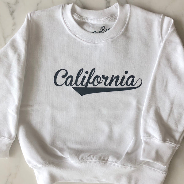 On The Rise CALIFORNIA Pullover Sweatshirt. White sweatshirt with black text stating California in cursive text