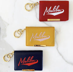 Chaos leather card holder in red, yellow, and navy blue. They all have gold metal accent key rings and the word Malibu written across it.