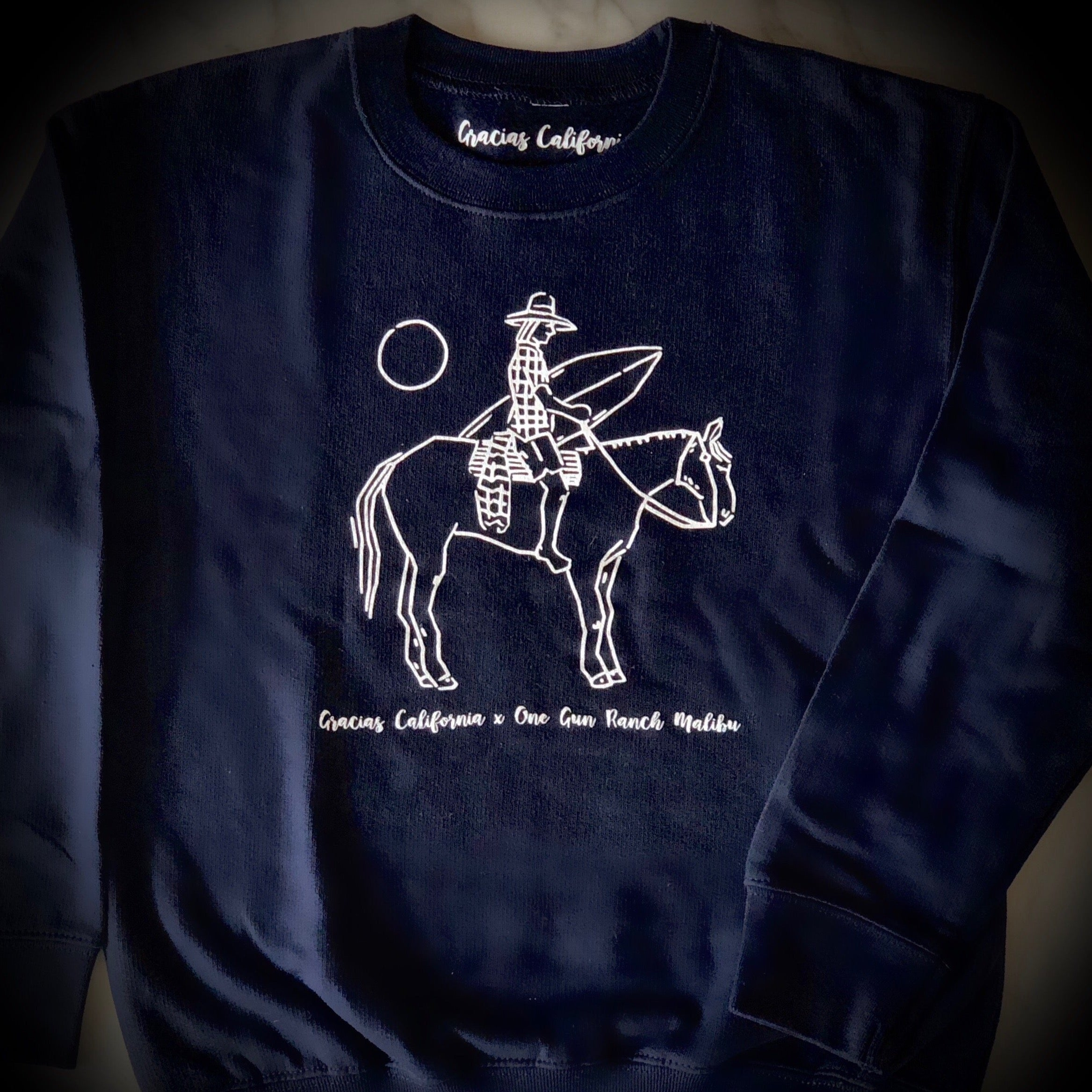 GC kids navy sweatshirt with a white outline of a woman riding a horse and holding a surfboard. At the bottom the text says gracias california X one gun ranch malibu.