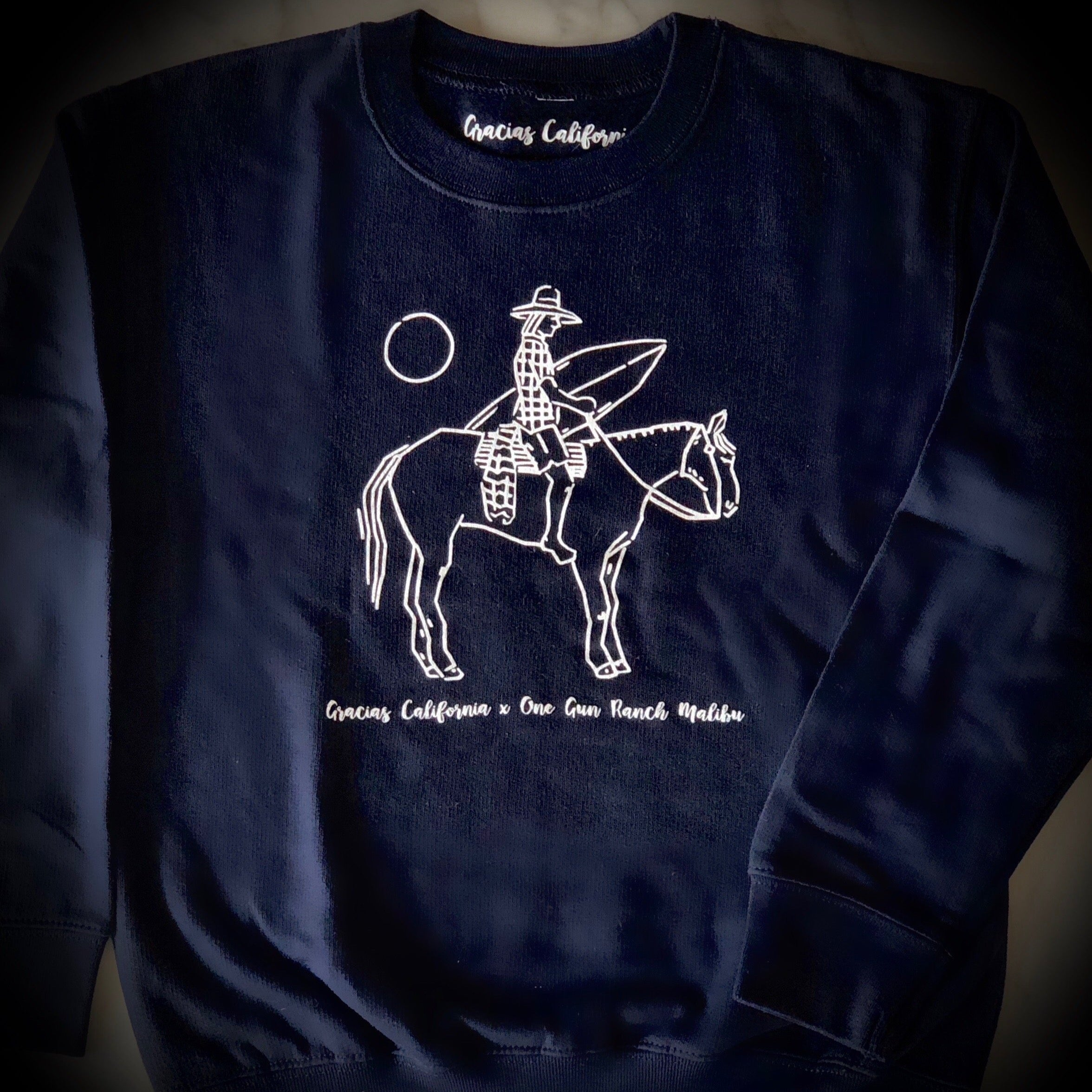 navy blue sweatshirt with a white outline design of a woman riding a horse and carrying a surfboard.