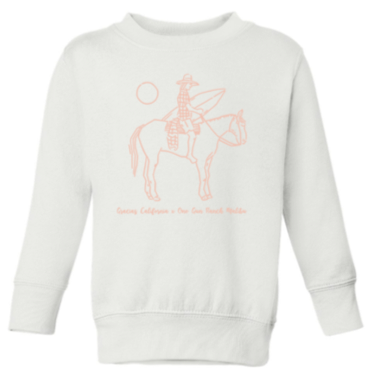 white sweatshirt with a pink outline drawing of a woman riding a horse and holding a surfboard. Underneath the text reads gracias california X one gun ranch malibu
