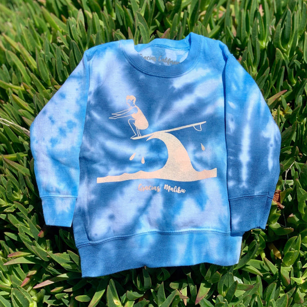 Gracias Malibu blue and white tiedye sweatshirt with a white print design of a man surfing on a wave crouching down at the end of a surfboard. The text at the bottom reads gracias Malibu.