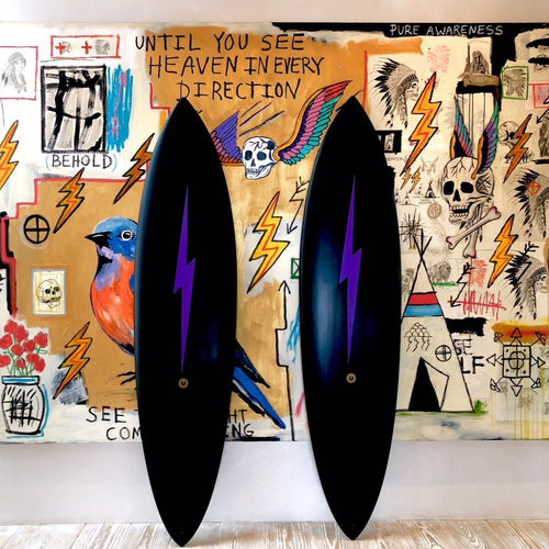 Two all black surfboards with a purple lightning bolt down the middle.