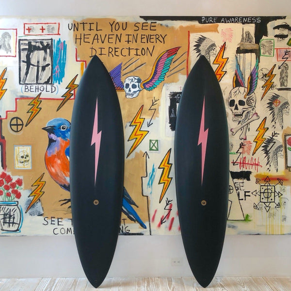 Two solid black surfboards with a long blush pink lightning bolt down the middle.