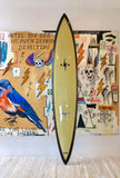 "Light yellow long board surfboard. There is a black trim around the outside. There is a black lightning bold on the upper portion of the board towards the nose. There is a white and black logo on the back half of the board that says ""One Gun Ranch."