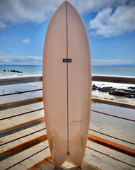 Light blush pink surfboard. The tail is split like a whale tale, there is a black line running down the middle from the tail to the tip. There is a black rectangle in the center of the board with the logo ALBUM in all white caps.