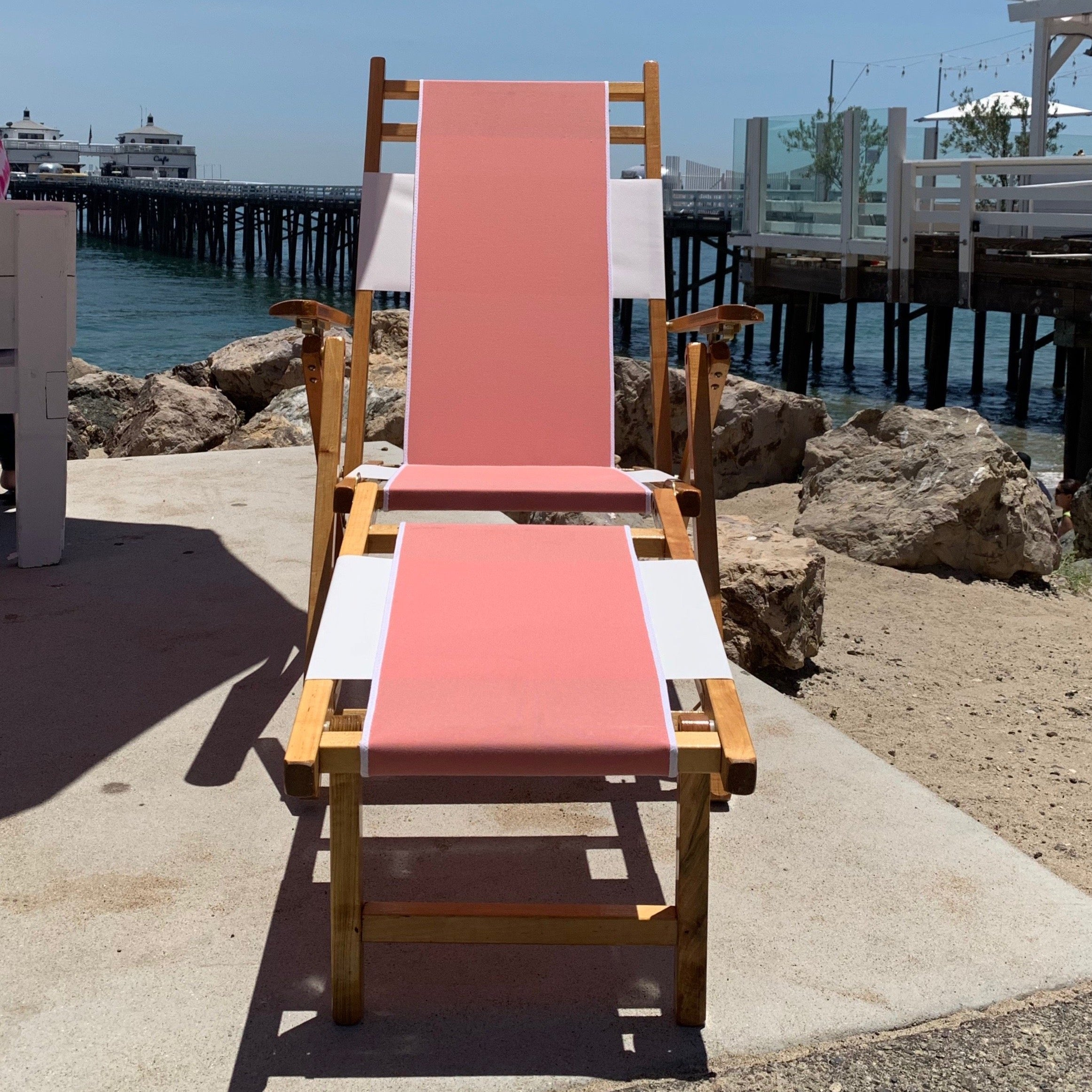 A folding beach chair made of wood. There's a pink strip of fabric running from the head rest to the end of the seat.