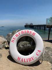 White lifesaver with the words Surfrider Malibu, CA in pink around it.