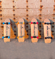One Gun Ranch Buckshot x Arbor Skateboards. Brown wood boards with The One Gun Ranch logo on the bottom. Wheels are blue, orange, pink, and black. Bearings are silver and black .