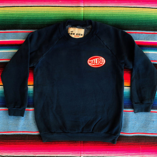 One Gun Vintage Malibu Kids Pullover. Navy sweater with Malibu printed on the left side.