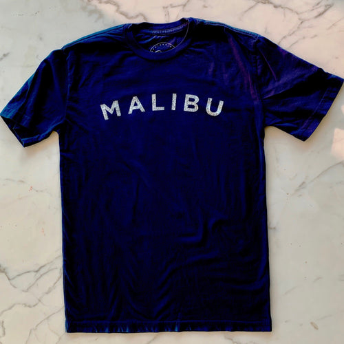 Blue Malibu t-shirt white letters. The word Malibu is written across the chest in a slight arc.