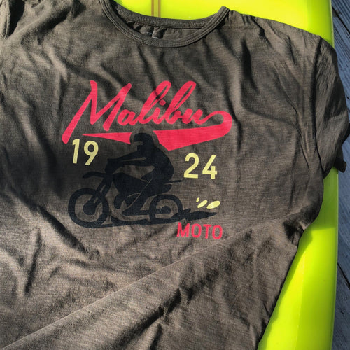 One Gun T- Shirts Malibu Moto 1924. Black shirt with Malibu Moto written in red text. A person rides on a motorcycle.