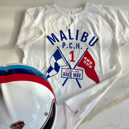 One Gun T-shirt Malibu PCH Raceway. White shirt with Malibu PCH mulholland race way written in blue text between two flags.