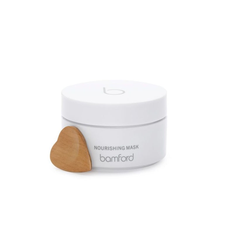 A white canister with a white twist on lid. It says Bamford Nourishing mask on it. A deeply hydrating treatment mask with powerful anti-ageing actives. Within a nourishing base of organic shea butter and coconut oil, soy stem cells help boost the production of collagen and elastin to promote youthful skin.
