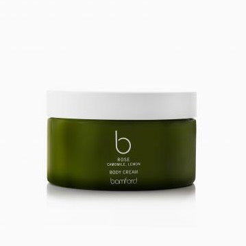 A wide green circle bottle with a a white twist on lid. It says Bamford rose camomile lemon body creme.