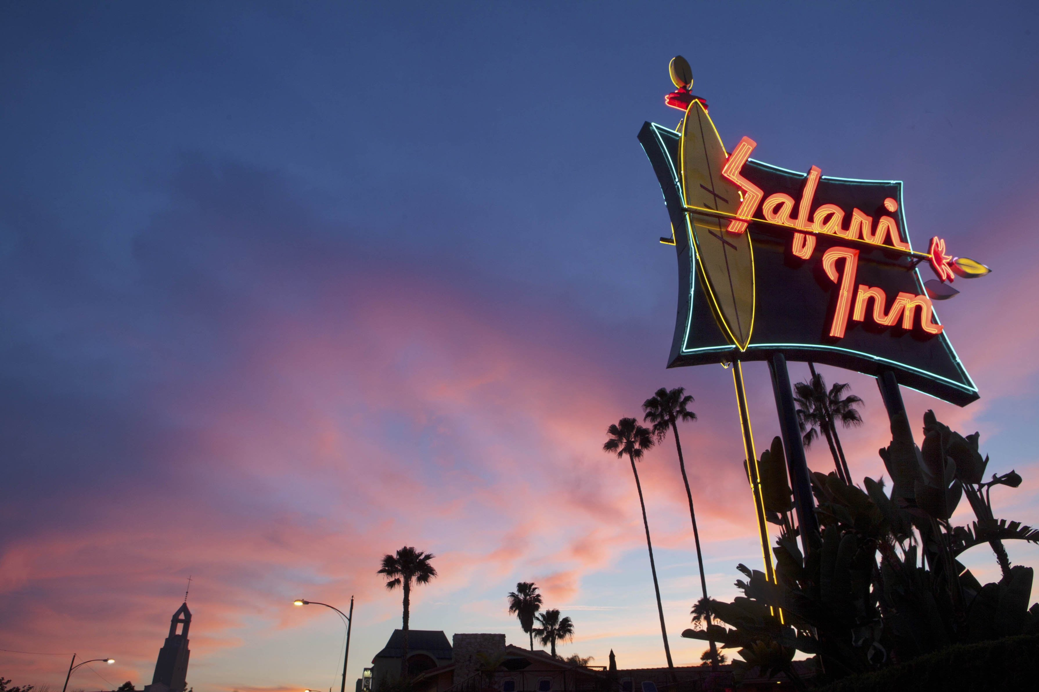 "A photograph of a neon sign located on the streets of Los Angeles. There clouds are pink and the sky is blue. There are buildings on the bottom and palm trees in the distance. The sign has a neon yellow outlined surfboard, and red neon lettering saying ""Safari Inn"""