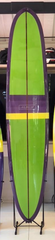 A long surfboard that's outlined with a thick dark purple border. It is primarily lime green, but has stripes of different shades of purple and yellow at the bottom. There is a dark purple line down the middle from nose to tail. The logo ALBUM is written in all white capitalized text in the center of the board.