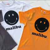 Grey, white and orange t-shirts with a black smily face in the center with the word Malibu underneath it.