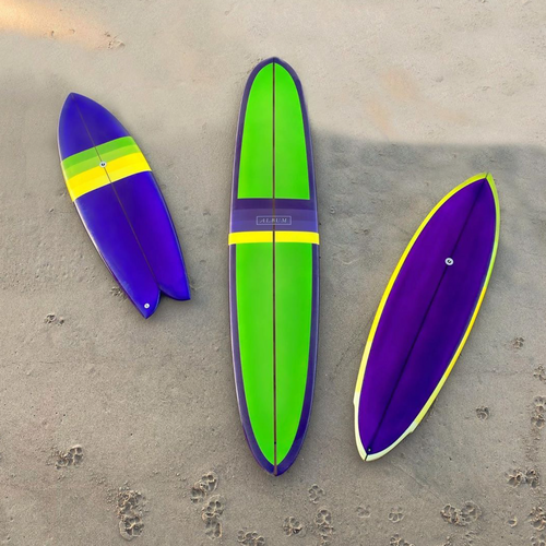 Three Album x One Gun Violet surfboards. The left is the smallest, the center is a long board, and the right is a medium board. They are all purple, green and yellow in design.