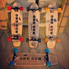 One Gun Ranch Buckshot x Arbor Skateboards. Brown wood boards with The One Gun Ranch logo on the bottom. Wheels are blue, orange, red, and black. Bearings are silver and black .