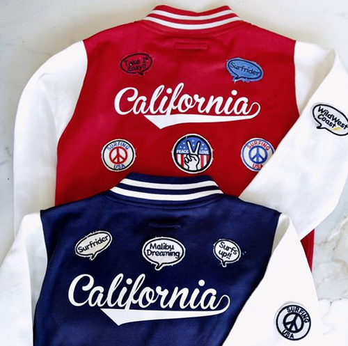 On The Rise California Varsity Jacket. One is red with white sleeves, the other is blue with white sleeves. On the back it says California in white cursive text and patches surrounding it.