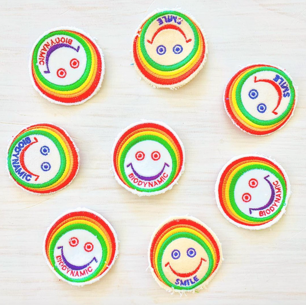 Recycled Cashmere Patch with a smiley face outlined in a rainbow pattern.