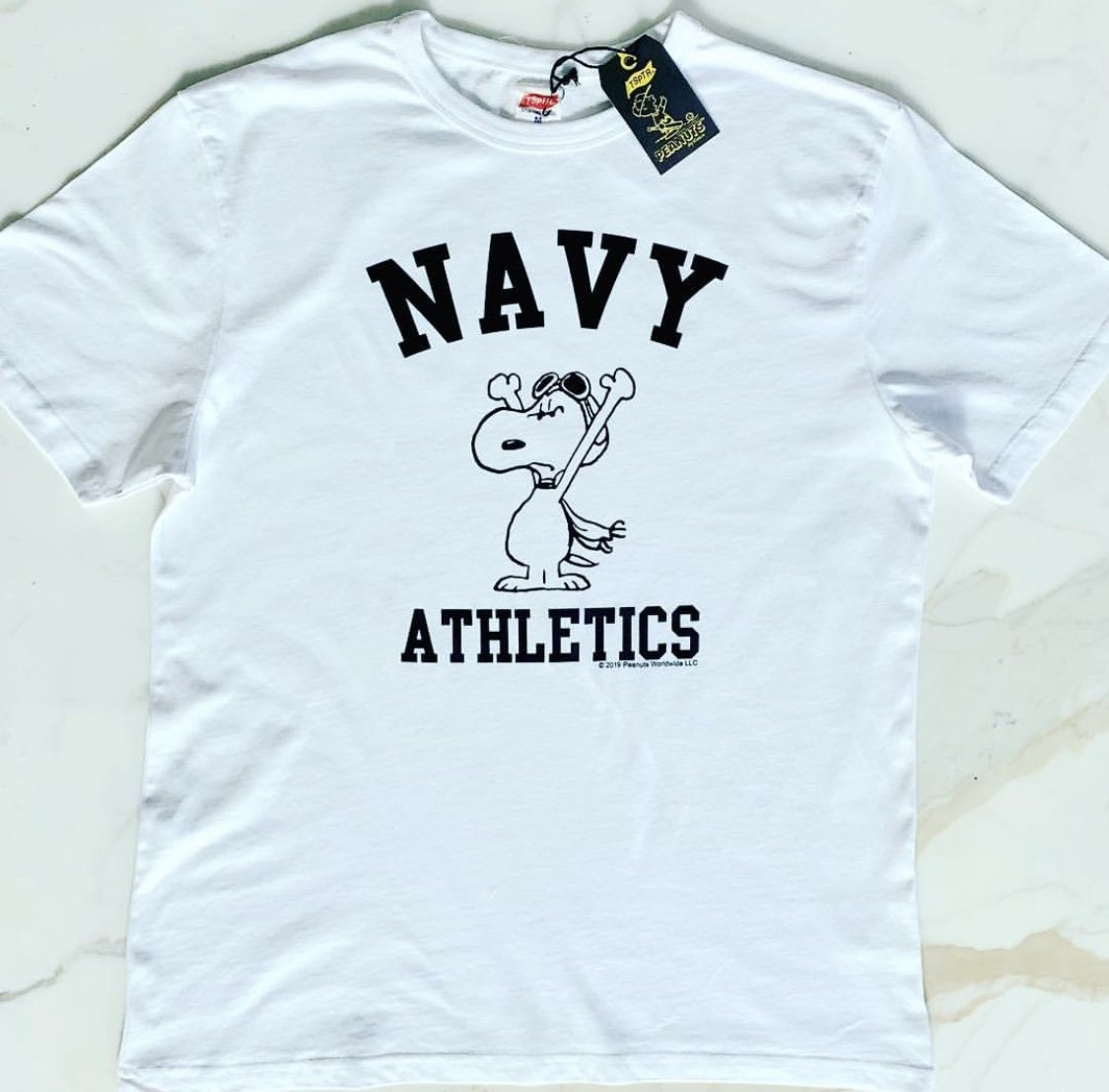 TSPTR Navy Athletics T-Shirt. White shirt with a design of Snoopy wearing aviator goggles on his head. The Words Navy Athletics prints next to him