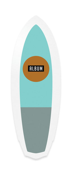 This surfboard is outlined with white around the edges. The main color is seafood blue on the top half, and a darker grey blue on the bottom half. There is a dark orange circle on the upper half, and a black rectangle in the middle of the circle. In the black rectangle is the logo Album.