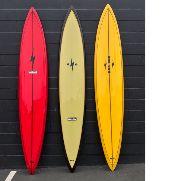 3 surfboards lined up. There's a red one on the left with a lightning bolt on the top center. The middle is a yellow board with black trim around the boarder. The right one is yellow with two lightning bolts and the logo One Gun in the middle.