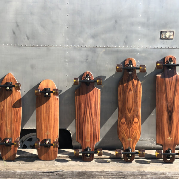 A line up of wood grain skateboards with black bearings and translucent honey brown wheels.