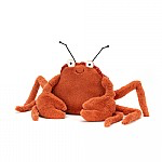 An orange fuzzy crab plush stuffed animal.