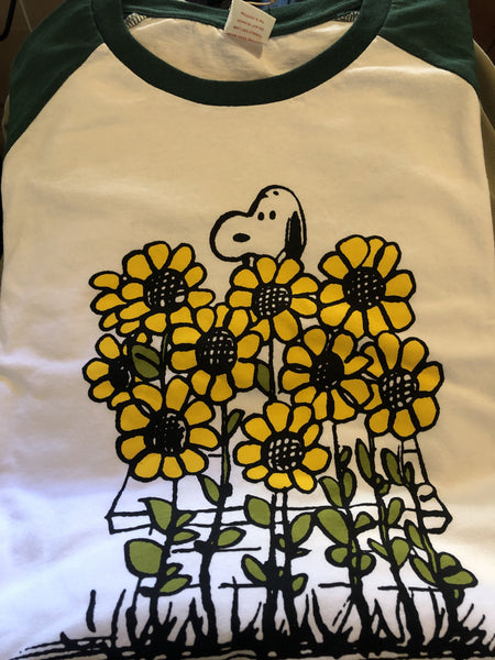 TSPTR Sunflowers Raglan T-Shirt. White shirt with green sleeves. It has a design of Snoopy in a field of tall sunflowers.
