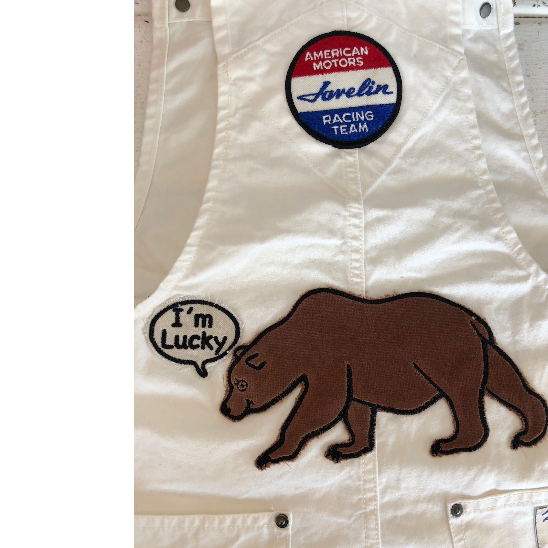 White denim overalls with an American motors racing team patch at the top. And a bear with a text bubble saying I'm Lucky on the bottom.