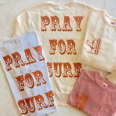 TSPTR PRAY FOR SURF T-Shirt. White shirt with the words Pray For Surf on it in orange letters on the back. Roadrunner holding a surfboard is on the front.